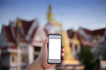 Hand holding smart phone and taking photo of Beautiful temple.