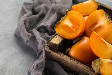 Delicious orange persimmons on wooden table .