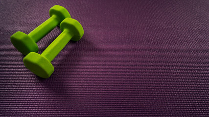 Yoga mat and dumbbells with space for text. Motivation