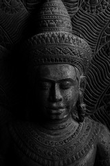 Dvaravati Buddha sculpture engrave from stone a style of Buddha with a Naga over His head by black and white photography