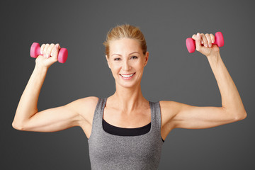 Fitness. Portrait of an attractive blond woman working out with dumbbell weights, toning her biceps while standing against isolated background.