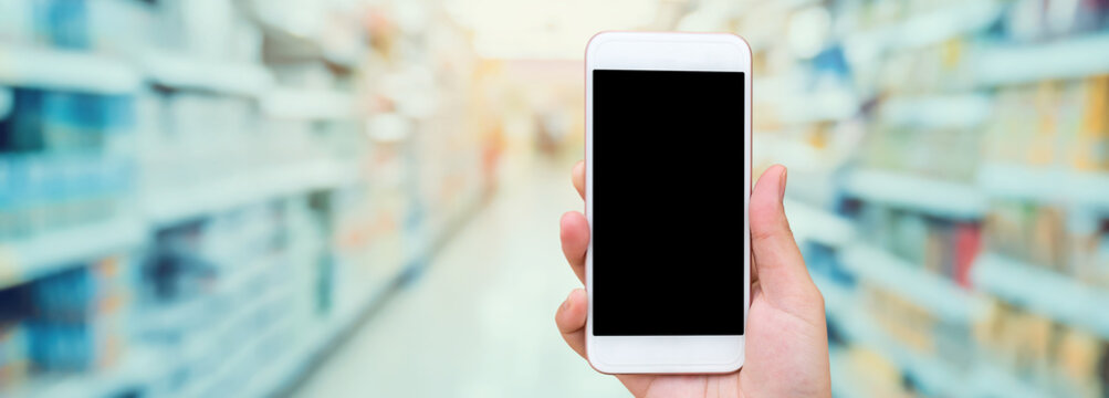 Female hand holding mobile phone with supermarket background