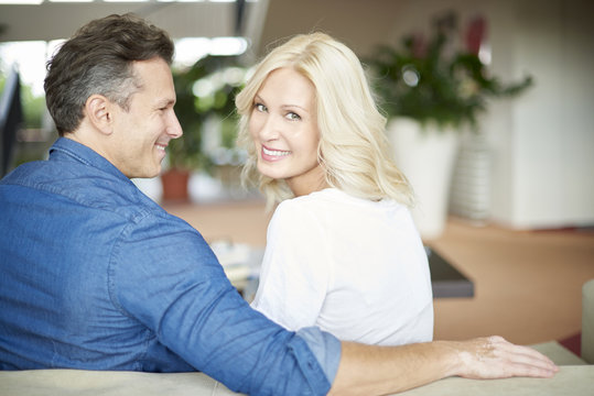 Rear view shot of a beautiful middle aged couple sitting on sofa at home and relaxing. Beautiful woman looking back while her husband hugging her.