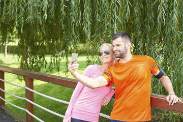 Runners. Shot of a happy young couple relaxing outdoors after running outdoors. Sporty young man using his mobile phone to taking selfie with his girlfriend.