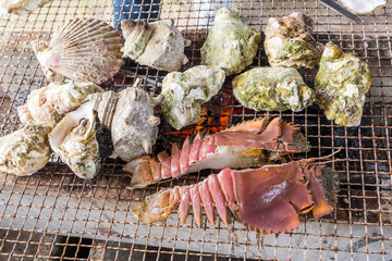 Sea food barbecue - fresh oyster, scallop and crayfish grill
