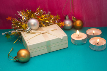 holiday gift box among candles and Christmas decorations on pink-blue background