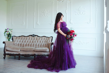 Beautiful pregnant woman in violet tender dress at luxury classic interior. Fashion pregnancy
