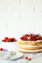 Delicious biscuit cake with berries on white wooden table