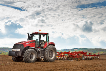 Fototapete - modern red tractor in the agricultural field.
