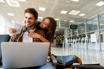 Excited girl showing travel documents to guy