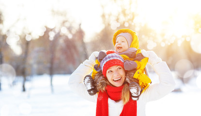 happy family mother and baby is happy snow on winter walk