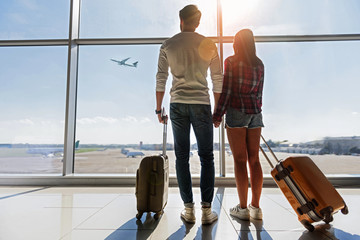Dreamful loving couple looking at flying plane