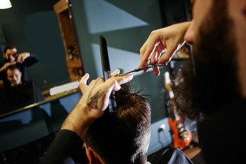 The Barber man in the process of cutting the client a pair of scissors in the Barbershop