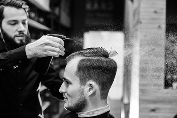 The Barber wets the client's hair spray sitting in a Barbershop, black and white photo