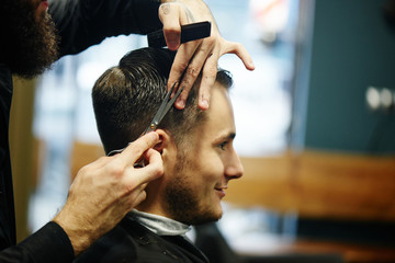 The Barber a man with a beard in the process of cutting the client a pair of scissors in the Barbershop