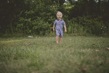 Baby boy walking on grassy field in park