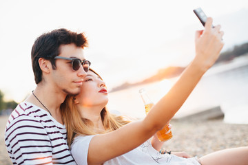 Young couple at the beach by the river, taking selfie