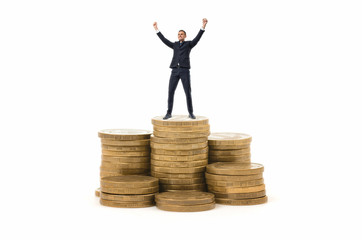 Businessman standing on stack of coins with his hands up in celebrating pose