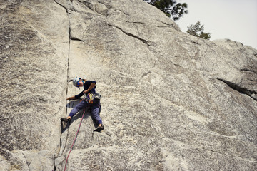 Low angle view of woman adjusting rope while climbing mountain