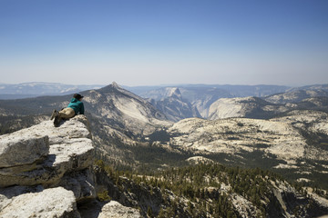 Woman relaxing on mountain against clear sky and looking at view