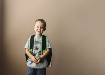 Portrait of happy boy with backpack standing against wall at home