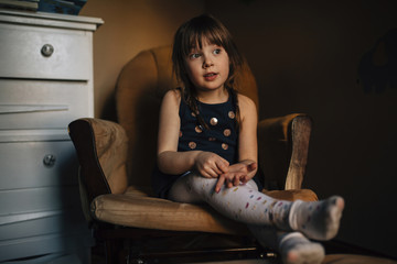 Girl sitting on chair at home