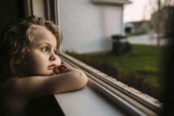Thoughtful girl looking away while leaning on window sill