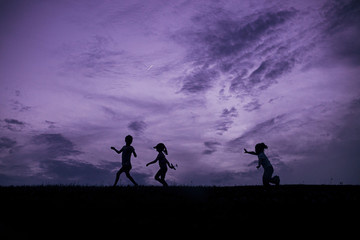 Happy sisters playing on field against dramatic sky during sunset