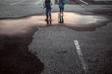 Low section of sisters playing in puddle