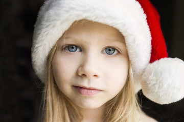 Portrait of cute girl in Santa hat against black background