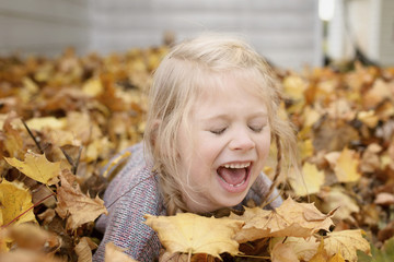 Cheerful girl playing with maple leaves during autumn