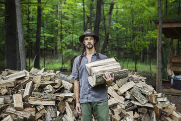 Portrait of man with firewood in forest
