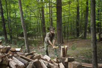 Man in hat cutting firewood with hammer in forest