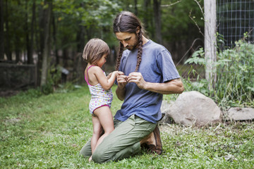 Father and daughter plaiting hair in backyard
