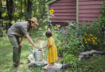 Father looking at girl filling water with hose in watering can