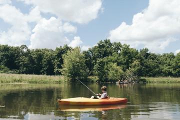 Boy fishing while sitting on boat in lake