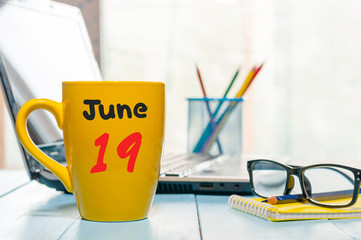 June 19th. Day 19 of month, color calendar on morning coffee cup at business workplace background. Summer concept. Empty space for text