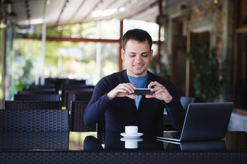 Young student man taking photo of a coffee cup and using laptop in canteen at the university or street cafe