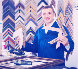 Man worker holding picture frame details on counter