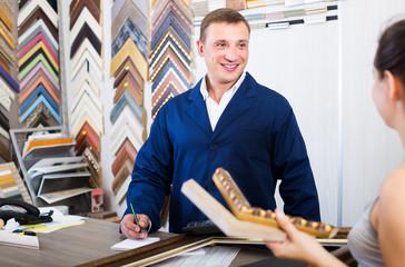 portrait of man seller taking order on picture frame from custom