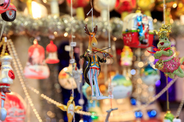 Colorful close up details of christmas fair market. Deer playing the violin balls decorations for sales.