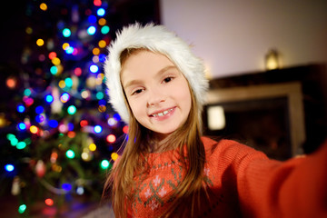 Happy little girl taking a selfie by a decorated Xmas tree
