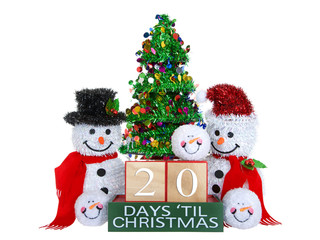 20 Days until Christmas light beech wood blocks with red trim on a green base with tinsel christmas tree, mr and mrs snowman and snowball snowmen heads isolated on a white background.