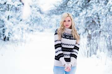 Beautiful young woman with blond hair is dressed in a warm black and white sweater. Snowy winter forest, christmas theme