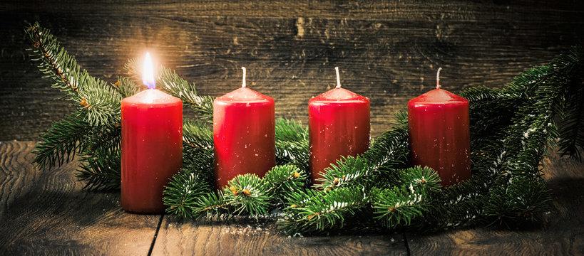 Ersterer Advent: eine leuchtende Kerze vor einem Holzhintergund