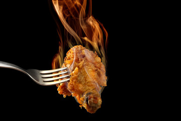 Fried chicken leg on black background with flame