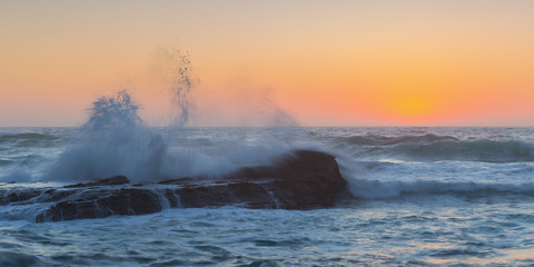 Waves breaking on a background of sea sunset.