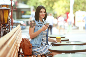 Young beautiful  girl sitting outdoors with cup of coffee