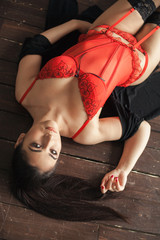 Young sexy woman lying on the wooden floor with eyes wide open in stockings and red corset