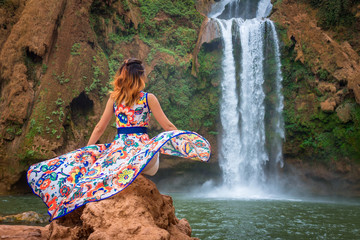 Beautiful waterfall in Morocco. Back of woman in beautiful dress looking fall Ouzoud. Exotic nature of North Africa,